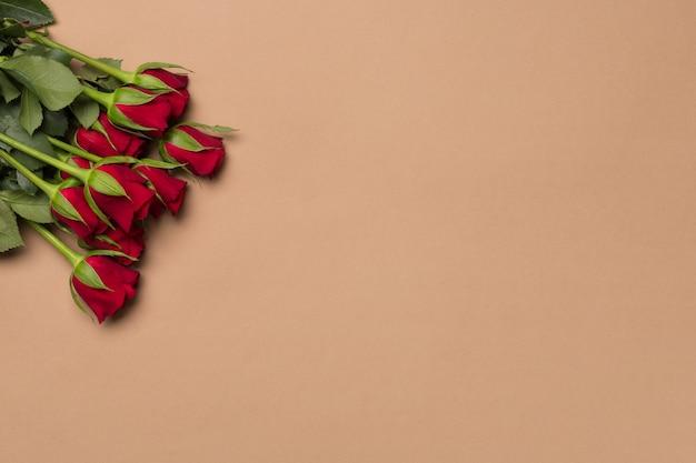 As rosas vermelhas florescem no backgroung bege, copiam o espaço.