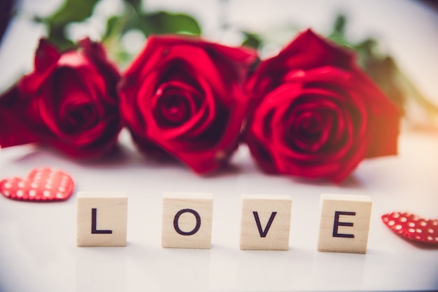 As rosas vermelhas são colocadas em um fundo branco e as letras de madeira forraram a palavra