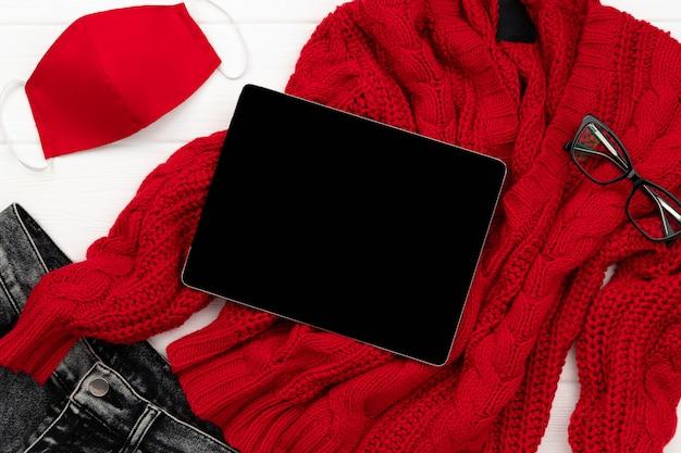 As roupas de inverno outono das mulheres olham com máscara protetora na mesa de madeira branca. vista plana leiga nova composição de moda normal.