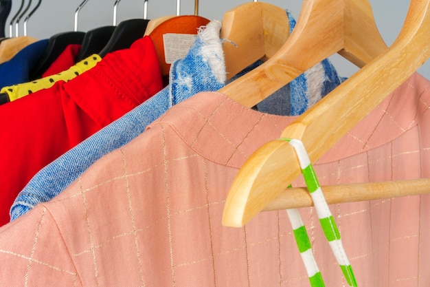 As roupas diferentes coloridas da mulher em cabide close-up
