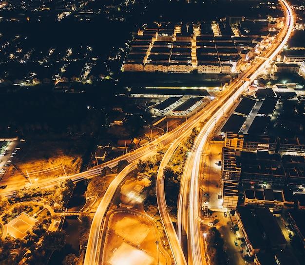 As ruas ao redor da cidade com luz noturna são tomadas de alto ângulo.