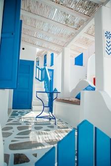 As ruas estreitas da ilha com varandas azuis, escadas e flores na grécia