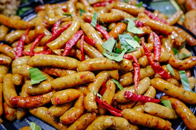 As salsichas ervais picantes tailandesas cozinharam recentemente em uma bandeja para a venda no mercado local.