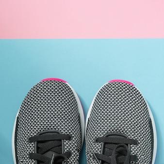 As sapatilhas da mulher encontram-se em uma superfície multi-colorida do rosa pastel e do azul. vista do topo.