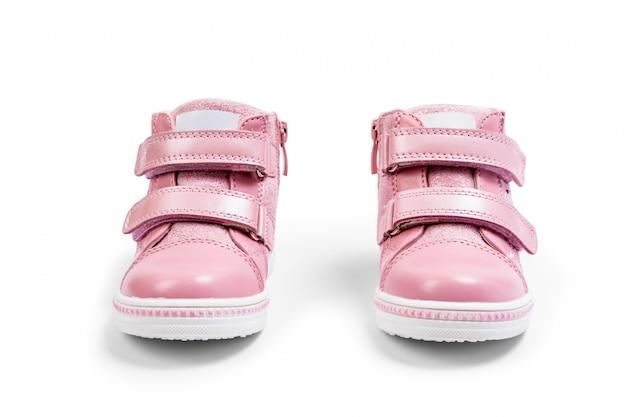 As sapatilhas das crianças-de-rosa isoladas em um branco