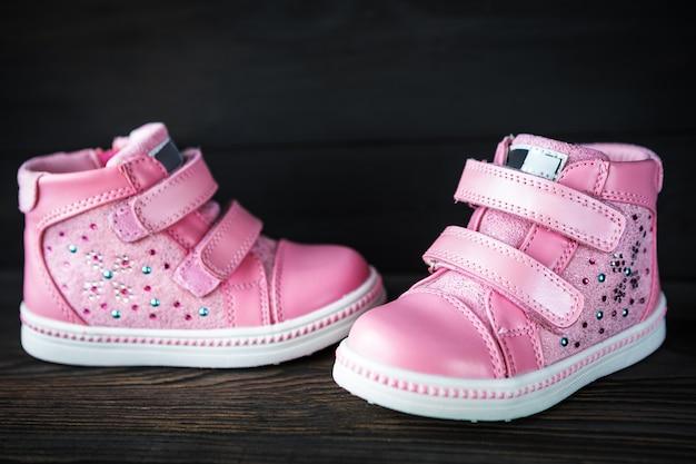 As sapatilhas das crianças-de-rosa isoladas em um fundo preto de madeira