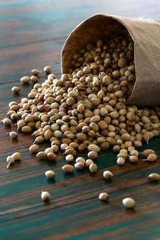 As sementes de coentro secadas orgânicas no saco de papel ensacam no fundo rústico colorido.