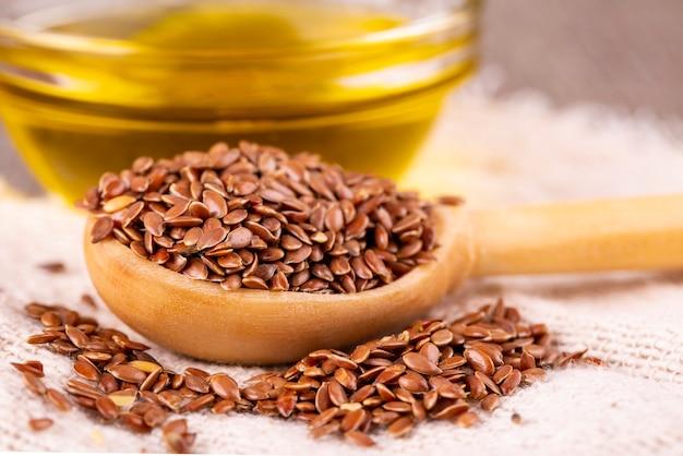 As sementes de linho marrons e óleo de linhaça em uma superfície de madeira