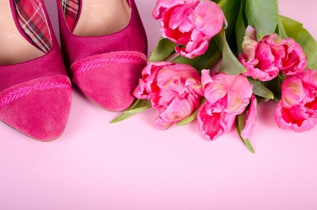 As senhoras sapato de salto alto rosa e tulipas. mulher com espaço da cópia, símbolo do conceito para o dia da fêmea, do amor, dos valentim e das mulheres, foco macio.
