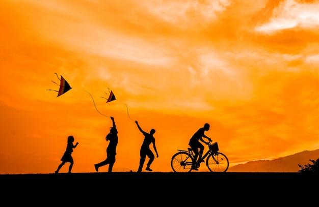 As silhuetas das crianças jogam com papagaios e ciclistas no por do sol.