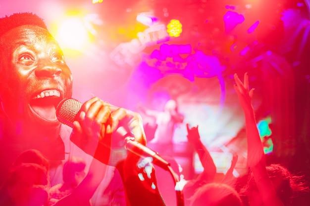 As silhuetas desfocadas da multidão do show em frente às luzes brilhantes do palco