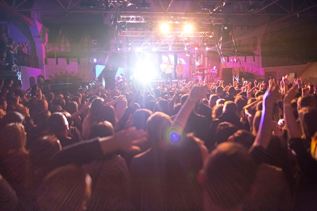 As silhuetas do show se aglomeram diante das luzes brilhantes do palco. concerto de uma banda de rock abstrato