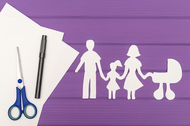 As silhuetas recortadas em papel de homem e mulher com criança e carrinho de bebê