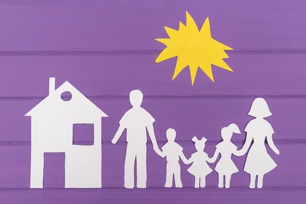 As silhuetas recortadas em papel de homem e mulher com duas meninas e menino sob o sol, casa perto