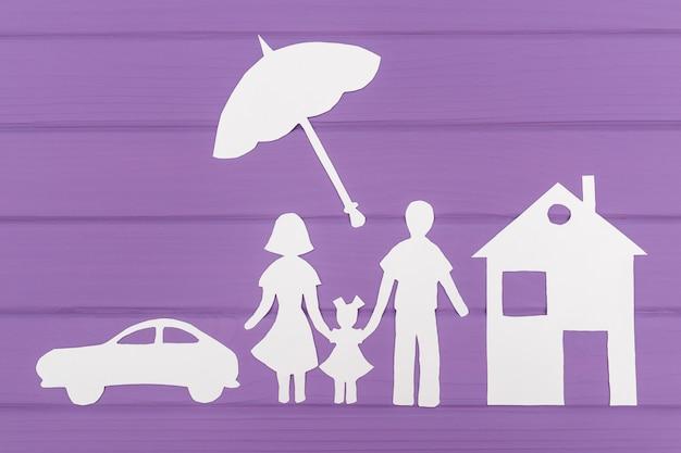 As silhuetas recortadas em papel de homem e mulher com uma garota sob o guarda-chuva, casa e carro perto