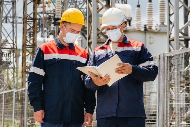 As subestações elétricas dos engenheiros realizam uma pesquisa de modernos equipamentos de alta tensão na máscara no momento da pandemia. energia. indústria.