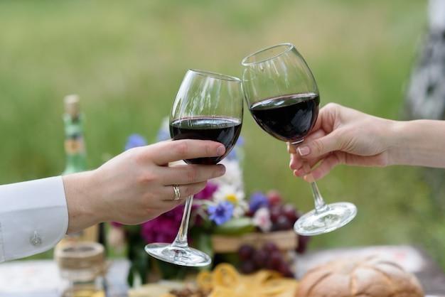 As taças de vinho com as mãos dos noivos