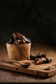 As tâmaras são servidas em uma mesa de madeira. fruta típica do oriente médio, geralmente comida ao quebrar o jejum