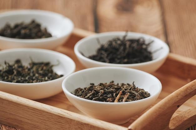 As tigelas brancas de variedade de chá seco em ordem no fundo de madeira