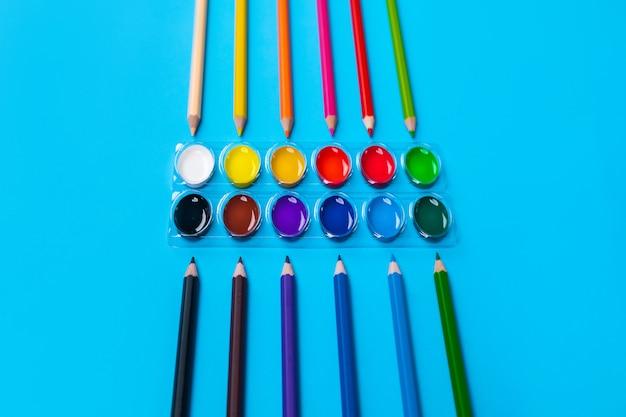 As tintas guache brilhantes para desenho localizadas no centro em um azul ao redor espalham lápis coloridos brilhantes dispostos verticalmente. fechar-se.