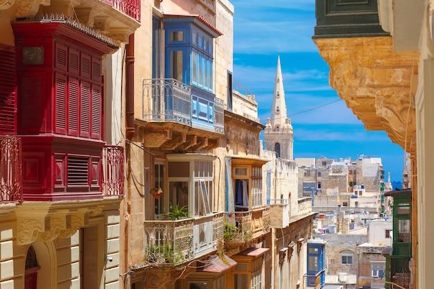 As tradicionais varandas de madeira coloridas maltesas e a pró-catedral anglicana de são paulo em valletta, malta