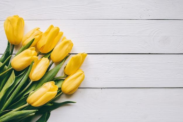 As tulipas amarelas ajuntam-se no backgropund rural da tabela do celeiro rústico de madeira das pranchas. espaço vazio para letras, texto, cartas, inscrição. modelo horizontal bonito cartão postal leigos.
