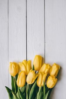 As tulipas amarelas ajuntam-se no backgropund rural da tabela do celeiro rústico de madeira das pranchas. espaço vazio para letras, texto, cartas, inscrição. modelo vertical bonito cartão postal leigos plana.