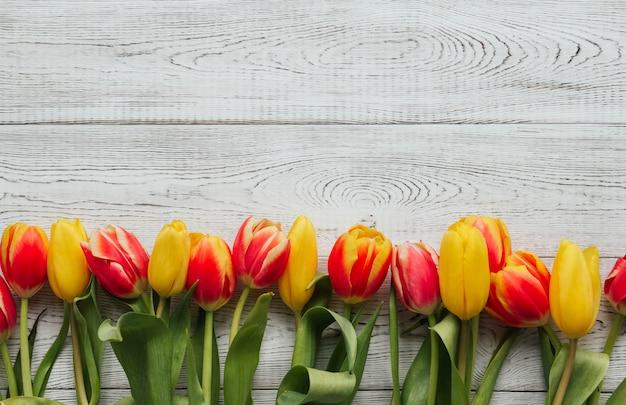 As tulipas amarelas, cor-de-rosa e vermelhas em um fundo de madeira branco copiam o espaço. fronteira de tulipa.