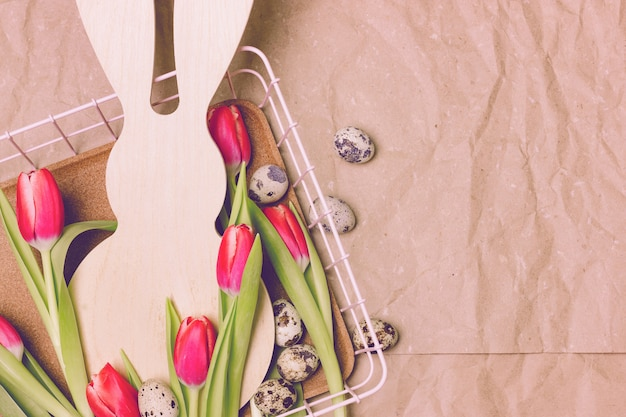 As tulipas cor-de-rosa adiantadas com um coelho dão forma em um fundo de papel bege. ovos de codorna mentem ao redor