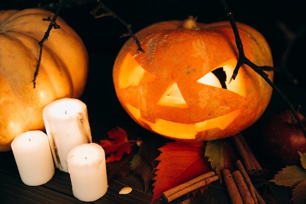 As velas brancas estão de pé antes de assustar a abóbora de halloween na canela
