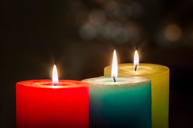 As velas coloridas vermelhas, amarelas e verdes com bokeh borrado natal e ano novo copiam o espaço.