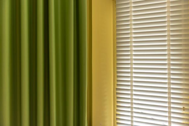 As venezianas pela janela ou pela janela das cortinas e pela cortina verde, cegam o conceito da decoração da janela.