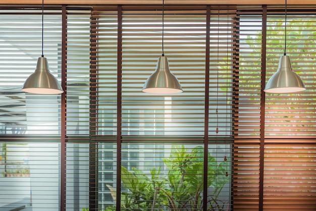 As venezianas pela janela ou pela janela das cortinas e pelo feixe da lâmpada do teto, cortam o conceito da decoração da janela.
