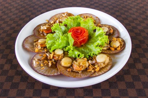 As vieiras fritadas com o alho decorado com cenouras em um prato cerâmico branco puseram sobre o assoalho de couro.