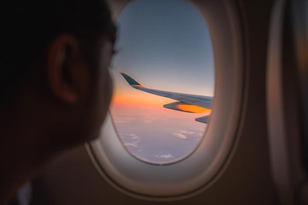 Asa da silhueta de um avião na opinião do nascer do sol através da janela.