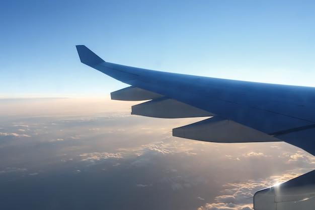 Asa de avião acima das nuvens ao pôr do sol.