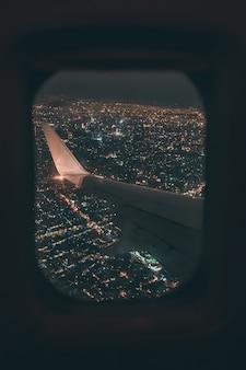 Asa de avião com as luzes da cidade