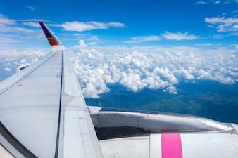 Asa de avião com nuvem de céu azul
