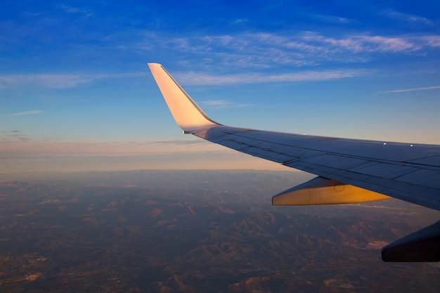 Asa de avião de jato ao pôr do sol com luz do sol dourado