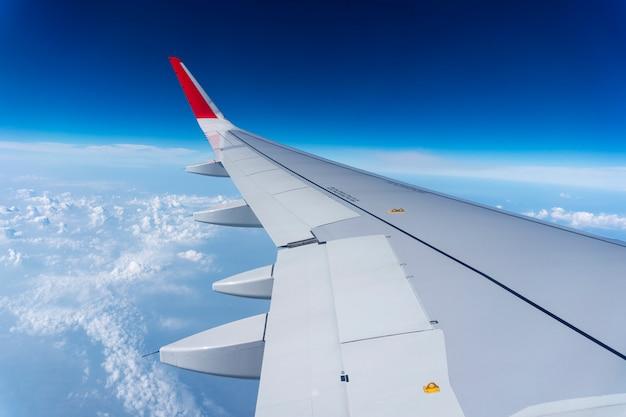 Asa de avião no céu azul e nuvens