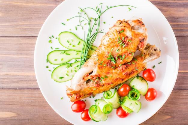 Asa de peru assada, fatias de pepino e tomate cereja em um prato sobre uma mesa de madeira. vista do topo