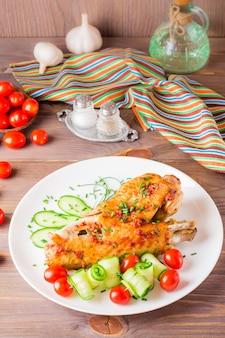 Asa de peru assado, fatias de pepino e tomate cereja em um prato sobre uma mesa de madeira