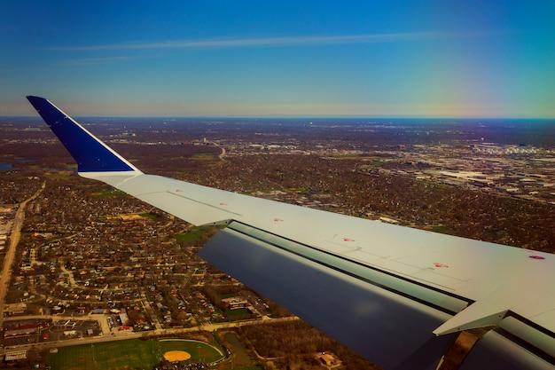 Asa de um avião voando acima das nuvens e do solo