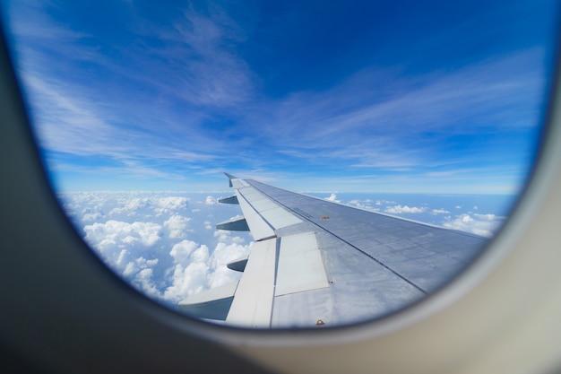 Asa de um avião voando acima das nuvens olhar da janela da cabine
