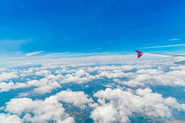 Asa de um avião voando acima das nuvens.