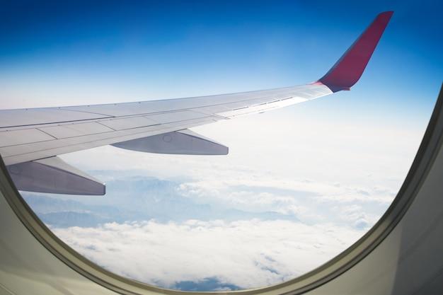 Asa de um avião voando acima do céu