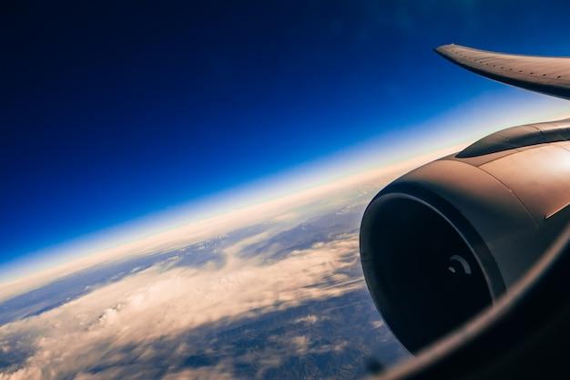 Asa e turbina da aeronave através da janela contra o céu com nuvens