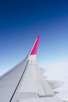 Asa vazia de um avião voando contra o céu azul brilhante