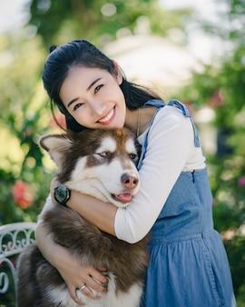 Asain bela jovem abraçando seu cachorro