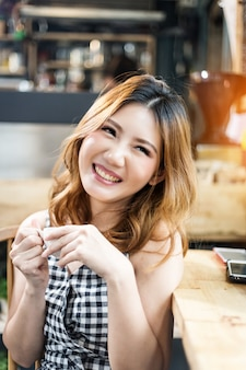 Asain beldade garota feliz em verificador vestido sorrindo com cofee quente na cafeteria